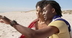 Couple wrapped in American flag sitting together on the beach 4k. Side view of African american couple wrapped in American flag sitting together on the beach stock video