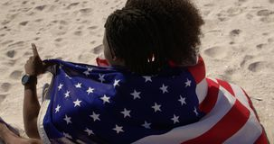 Couple wrapped in American flag sitting together on the beach 4k. Side view of African american couple wrapped in American flag sitting together on the beach stock footage