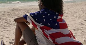 Side view of African american couple wrapped in American flag sitting together on the beach 4k stock video footage