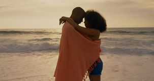 Side view of African American couple wrapped in blanket on the beach 4k. Side view of African American couple wrapped in blanket on the beach. They are embracing stock video