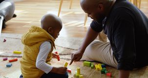 Father and son playing with building blocks in a comfortable home 4k