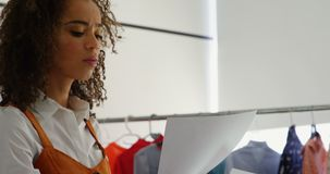 Side view of African American female fashion designer holding sketch sheet in workshop 4k stock footage