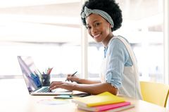 Female graphic designer using graphic tablet and laptop. Side view of African american female graphic designer using graphic tablet and laptop at desk in office royalty free stock images
