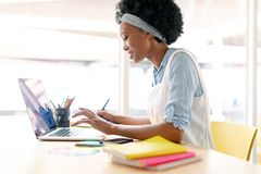 Female graphic designer using graphic tablet and laptop royalty free stock image