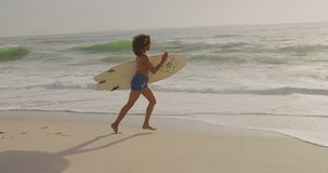 Side view of African American female surfer running with surfboard on the beach 4kSide view of Afric. Side view of African American female surfer running with stock video footage