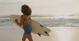 Side view of African American female surfer running with surfboard on the beach 4k. Side view of African American female surfer running with surfboard on the stock footage