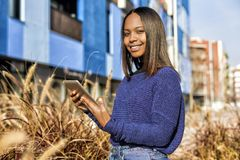 Side view of an African-American girl standing, while holding the tablet in her hands and looking camera royalty free stock images