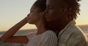 Man embracing woman at beach during sunset 4k stock footage