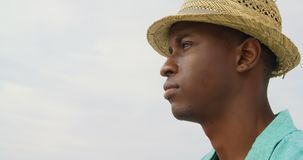 Side view of African American man in hat standing on the beach 4k. Side view of African American man in hat standing on the beach. He is looking away 4k stock video