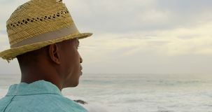 Side view of African American man in hat standing on the beach 4k. Side view of African American man in hat standing on the beach. He is looking away 4k stock footage