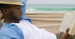 Side view of African american man reading a book on the beach 4k. Side view of African american man reading a book on the beach. He is relaxing in a hammock 4k stock video footage