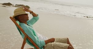 Side view of African american man relaxing in a sun lounger on the beach 4k. Side view of African american man relaxing in a sun lounger on the beach. He is stock footage