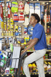 Side view of African American man with shopping cart at hardware store Royalty Free Stock Photos