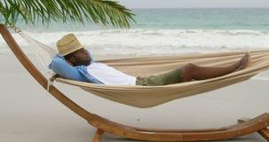 Side view of African american man sleeping in a hammock on the beach 4k. Side view of African american man sleeping in a hammock on the beach. He is asleep 4k stock video