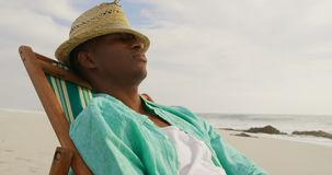 Side view of African american man sleeping in a sun lounger on the beach 4k. Side view of African american man sleeping in a sun lounger on the beach. He is stock footage