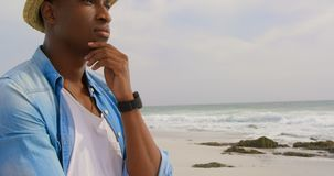 Side view of African american man standing with hand on chin at beach 4k. Side view of African american man standing with hand on chin at beach. He is looking stock video footage