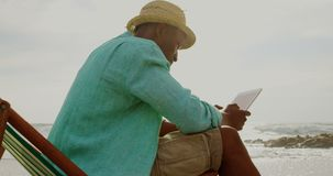 Side view of African american man using digital tablet on the beach 4k. Side view of African american man using digital tablet on the beach. He is relaxing in a stock footage