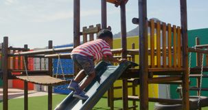 Side view of African American schoolboy playing on slides in the school playground 4k. Side view of African American schoolboy playing on slides in the school stock footage