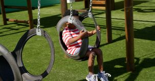 Side view of African American schoolboy playing on a swing in school playground 4k. Side view of African American schoolboy playing on a swing in school stock video footage