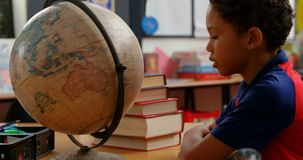 Side view of African American schoolboy studying globe at desk in classroom at school 4k. Side view of African American schoolboy studying globe at desk in stock footage