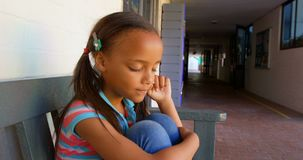 Side view of African American schoolgirl sitting on bench and crying in school corridor 4k stock video