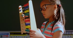 Side view of African American schoolgirl with spectacle learning math with abacus in classroom 4k stock footage