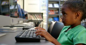 Side view of African American schoolgirl using computer in library at school 4k. Side view of African American schoolgirl using computer in library at school stock video footage