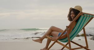 Side view of African american woman relaxing in a sun lounger on the beach 4k. Side view of African american woman relaxing in a sun lounger on the beach. She is stock footage