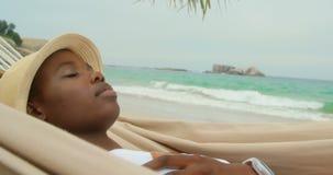 Side view of African american woman sleeping in a hammock on the beach 4k. Side view of African american woman sleeping in a hammock on the beach. She is asleep stock footage