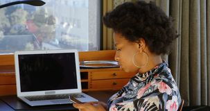 Woman using  mobile phone at home 4k. Side view of African American woman using mobile phone at home. Father and son playing in the background. 4k stock footage