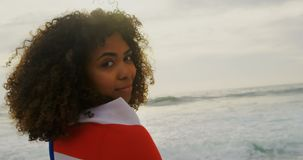 Side view of African American woman wrapped in American flag standing on the beach 4k. Side view of African American woman wrapped in American flag standing on stock video footage