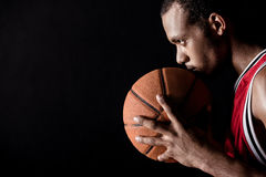 Side view of african sporty man holding basketball ball. On black royalty free stock image