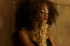Side view African woman with gold makeup and necklace, laying hands on her chin eyes closed, bronze wall background Royalty Free Stock Images