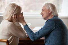 Side view aged husband touching stroking face of beloved wife stock photos
