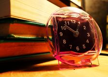 Side view of an alarm clock standing next to a pile of books on a wooden surface stock image