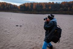 Side view of amateur photographer shooting the autumn scenery of the forest road. Landscape therapy. Photo hunting concept stock photography