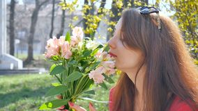 Side view of amazing and beautiful young woman holding a big bouquet of colorful flowers outdoors near yellow bush on stock footage