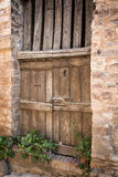 Side view of ancient wooden door decorated with plants Stock Photo