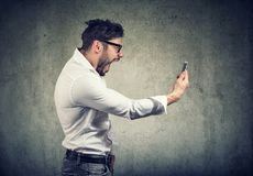 Angry man holding smartphone and shouting in anger. Side view of angry man holding smartphone and shouting in anger on gray background royalty free stock images