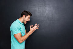 Side view of a angry man screaming over black background Stock Image