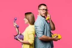 side view of angry young couple standing back to back and talking by rotary phones isolated