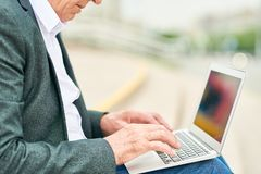 Crop businessman using laptop on street stock photos