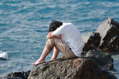 Side view of anxiety stressed Asian man hug his knee and sitting at sea shore. Side view of anxiety stressed Asian man hug his knee and sitting at sea shore Royalty Free Stock Image