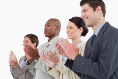 Side view of applauding businessteam. Standing together against a white background stock photos