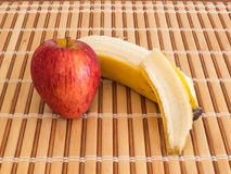 Side view of apple and peeled banana. Natural and healthy food. Side view of apple and peeled banana, on wooden slat table Royalty Free Stock Photo