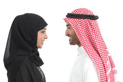 Side view of an arab saudi couple looking each other. Isolated on a white background Royalty Free Stock Photo