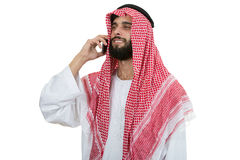 Side view of an arab saudi emirates man using a smart phone. stock images