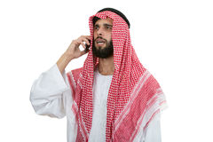 Side view of an arab saudi emirates man using a smart phone. stock image