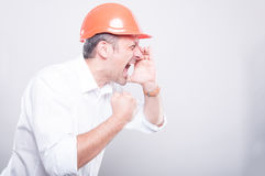 Side view of architect wearing  hardhat screaming out loud. On grey background with copy text space Royalty Free Stock Photography