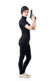 Side view of armed tough woman holding gun looking at camera. Full body length portrait isolated over white studio background stock images